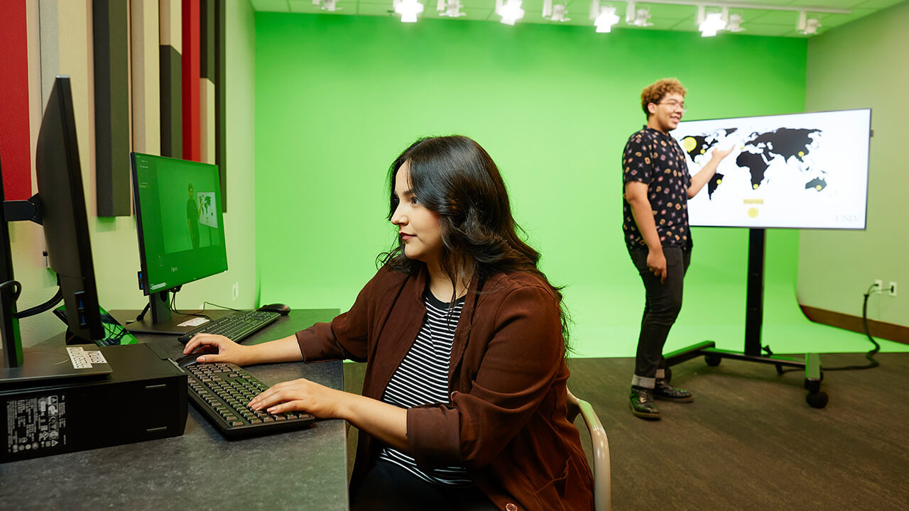 Woman sitting at computer with recording equipment with green screen behind her