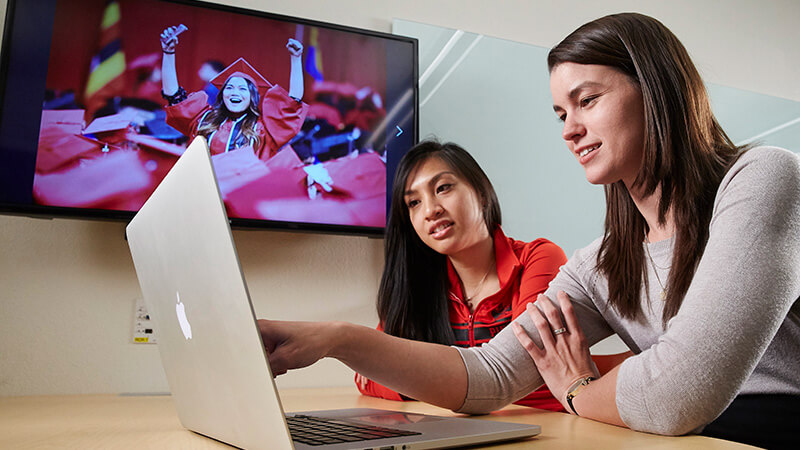 Two students looks at screen of laptop with TV screen showing students graduating in background