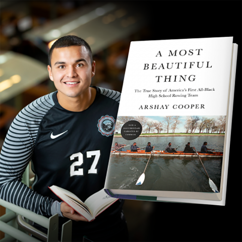 Student athlete posing with open book; book cover of A Most Beautiful Thing displayed in foreground