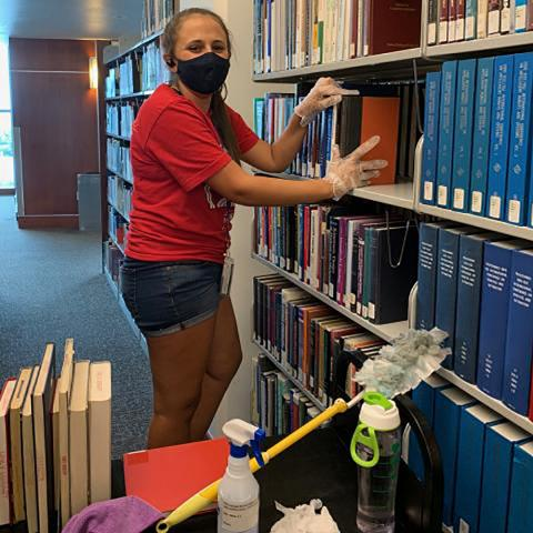 Student assistant wearing face mask and dusting book and sorting book shelves