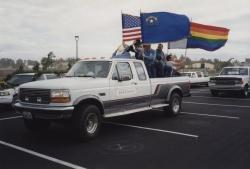 Example photograph from the Dennis mcBride Collection showing people standing in truck bed flying flags including the United States, Nevada, and Gay Pride.