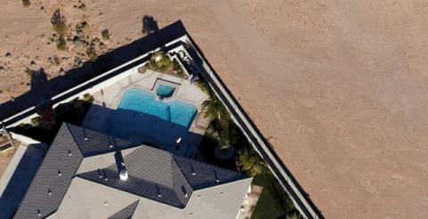 Aerial view of house with pool in backyard with nothing behind the house but dirt.
