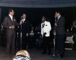 Example color photograph from the Dina at the Sands digital collection of the Rat Pack talking on stage.