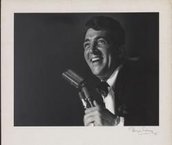 Example black and white photograph from Dino at the Sands digital collection of Dean Martin holding a microphone.