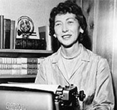 Example black and white photograph from the Florence and John Cahlan papers shows a woman smiling sitting behind a typewriter.