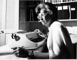 Example black and white photograph from the Jean Ford papers shows a woman sitting at a typewriter.