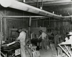 Example photograph from the Basic Magnesium Plant in Henderson showing men working inside a building.