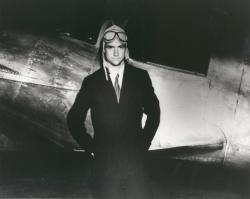 An example black and white photograph from the Welcome Home Howard digital collection showing Howard Hughes with aviator hat and goggles standing next to a plane.