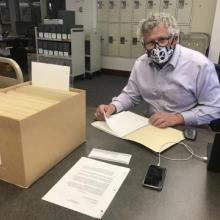 2021 Eadington Fellow, Dr. Fred Woods sitting at desk with archival files
