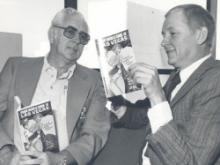 Hal Erickson with local journalist, Hank Kovell looking at a Las Vegas magazine.
