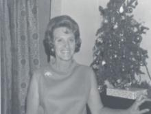Celesta Lowe standing in front of a Christmas tree.